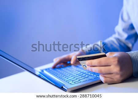 Close up of man using credit card to pay online