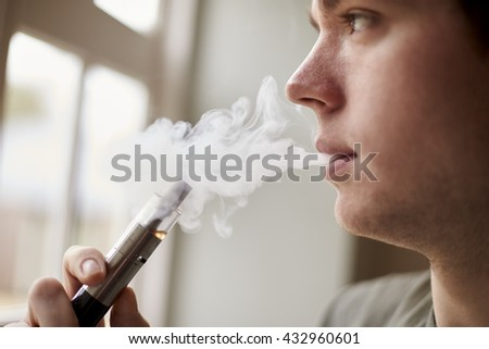 Close Up Of Man Using Vapourizer As Smoking Alternative - stock photo