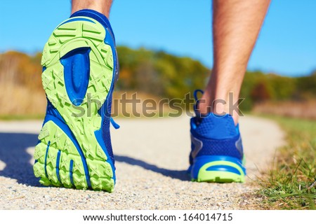 Close up of man walking on nature trail near forest preserve. Color image, copy space, male walking outside on a beautiful day in nature.Horizontal - stock photo