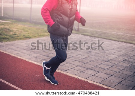 Close up of man wearing running clothes. Depth of field, selective focus, warm tone filter. Intentional motion blur and color shift