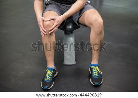 Close-up of man with an injured knee sitting in gym - stock photo