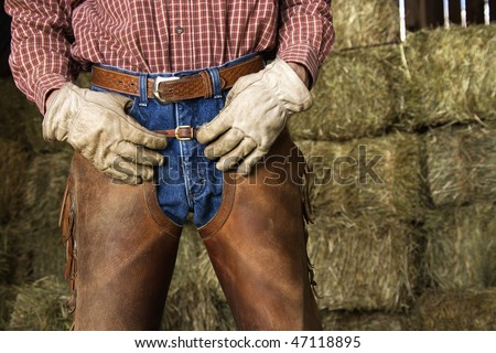 Close up of man with hands on his waist, wearing chaps and standing in front of hay bales. Horizontal shot.