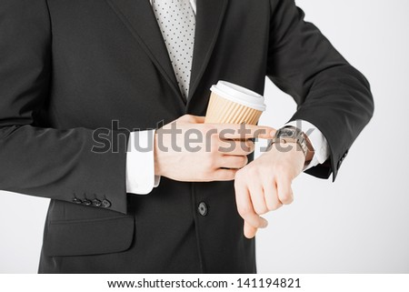 close up of man with take away coffee looking at wristwatch - stock photo