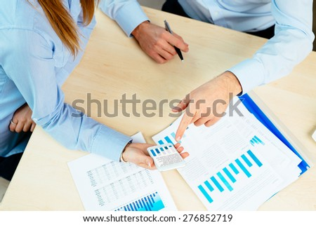 Close-up of managers hands holding a mobile and documents lying on a desk - stock photo