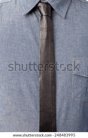 Close up of mans shirt and thin black leather tie - stock photo