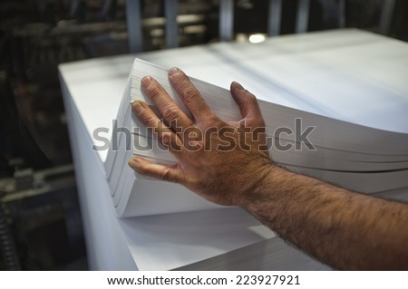 close-up of manually loading paper offset printing machine - stock photo
