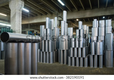close-up of manufactured silver metallic tubes stacked together upright, on the floor of an industrial hall