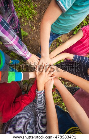 Close-up of many children's hands holding together as a team on a nature background