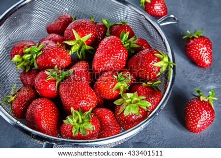 Close up of many fresh and juice strawberries in sieve - stock photo