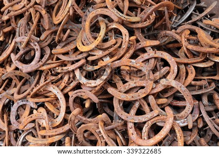Close-up of many old, rusted horseshoes - stock photo