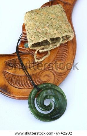 Close up of maori carved greenstone jade pendant with woven kite bag and wooden mere against white background