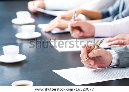 Close-up of masculine hand holding ballpoint over business document on background of human hands with cups of coffee near by