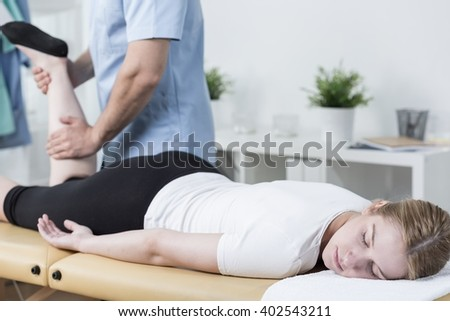 Close-up of masseur massaging female customer's leg - stock photo