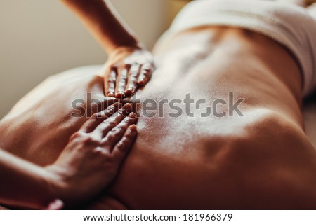 Close-up of masseur's hands and a client's back - stock photo