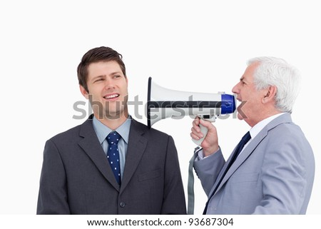 Close up of mature businessman with megaphone yelling at employee against a white background