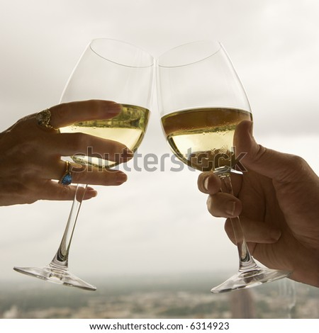 Close up of mature couple's hands toasting white wine. - stock photo