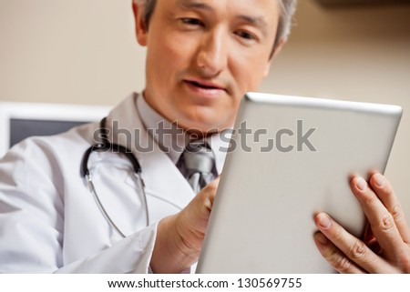 Close up of mature male doctor using digital tablet - stock photo