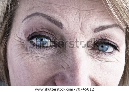 Close-up of mature woman blue eyes - stock photo