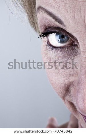 Close-up of mature woman  looking at camera, half face - stock photo