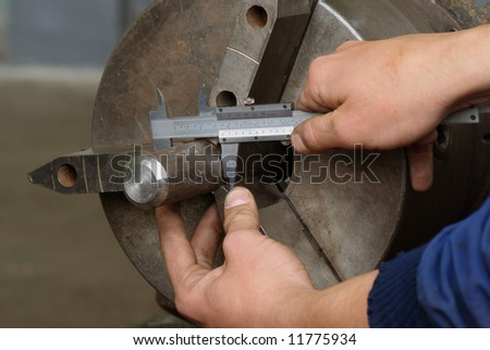 Close up of measuring metal part on lathe with caliper - stock photo