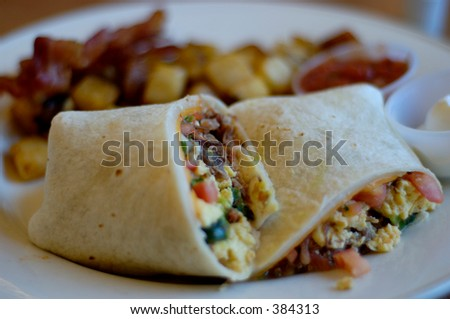 Close-up of meat burrito on plate with home fries and bacon. Shallow DOF, focus in center of burrito. - stock photo