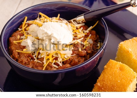 Close up of meat chili with red kidney beans, shredded cheese and sour cream in blue bowl with cornbread - stock photo
