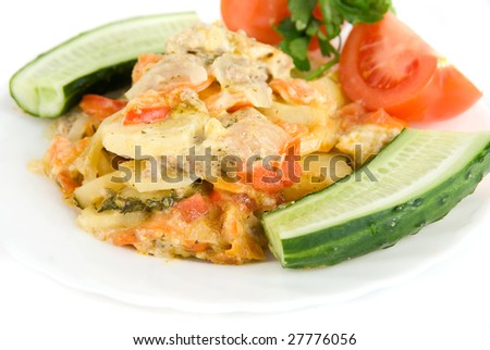 Close up of meat, potatoes, tomatoes and cucumbers dish on white