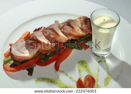Close-up of meat with vegetables garnish on a white plate on a black background studio - stock photo