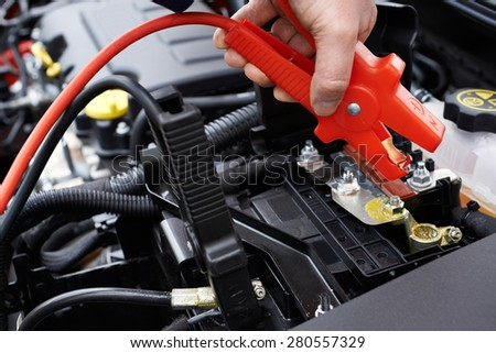 Close-Up Of Mechanic Attaching Jumper Cables To Car Battery - stock photo