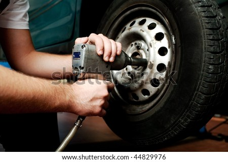 Close-up of mechanic changing wheel on car with pneumatic wrench. - stock photo