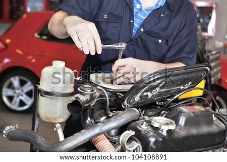 Close-up of mechanic repairing an engine in garage. - stock photo