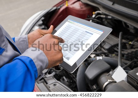 Close-up Of Mechanic With Digital Tablet Showing Graph While Examining Car - stock photo
