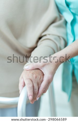 Close up of medic holding aged patients hand