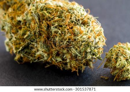Close up of medical marijuana buds sitting black background - stock photo