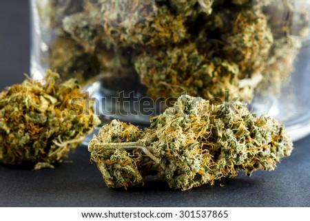 Close up of medical marijuana buds sitting next to glass jar on black background - stock photo