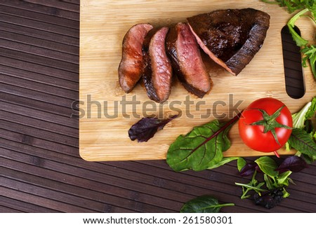 Close-up of Medium Rare Roast Beef with Fresh Herbs and  Vegetables - stock photo