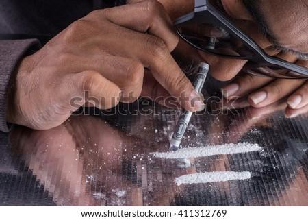 Close up of men enhancing cocaine into him nose. - stock photo