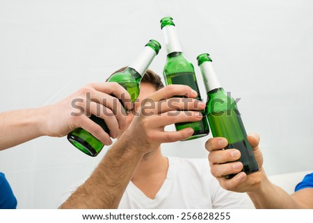 Close-up Of Men's Hand Toasting Beer Bottles - stock photo