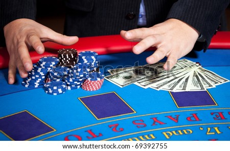 Close up of men's hand with chips, cards and one hundred dollars banknotes on poker table - stock photo