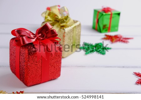 Close up of Merry christmas and Happy new year with gift box concept on white wooden background. Blank space, selective focus and decorated style.