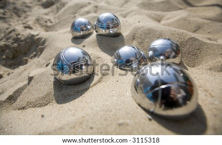 close-up of metal boccie balls in the sand - stock photo