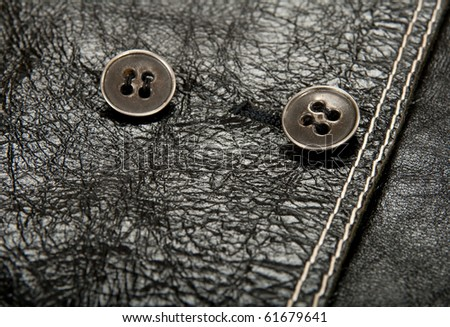 Close-up of metal buttons on shiny black leather clothing. - stock photo