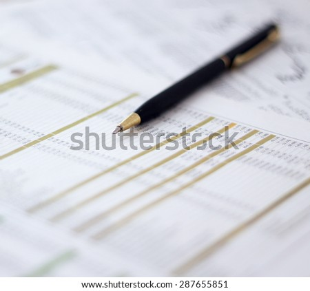 Close-up of metallic pen on document at workplace. Shallow depth of field. - stock photo