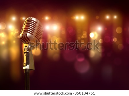 Close up of microphone in concert hall with blurred lights at background - stock photo