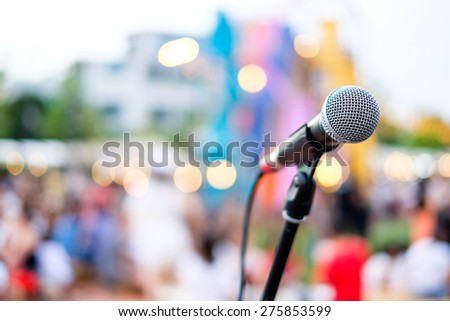 Close up of microphone in concert or conference room with blur people in the background - stock photo