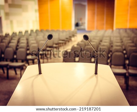 Close up of microphone in conference hall. Toned picture - stock photo