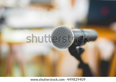 Close - up of microphone in conference room or concert hall with blur bokeh background , soft - focus.
