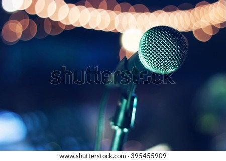 Close up of microphone on abstract bokeh light background at outdoor night party - stock photo