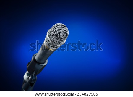 Close up of microphone on smooth blue background - stock photo