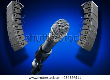 Close up of microphone on smooth blue background with speakers  - stock photo